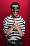 Angry burglar with handcuffs. Portrait on red background Stock Images