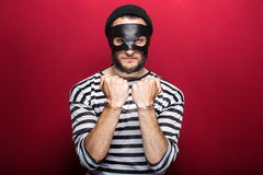 Angry burglar with handcuffs. Angry thief with handcuffs. Portrait on red background Stock Image