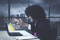 Angry business african american with error message. On his laptop royalty free stock image