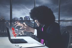Angry business african american with virus error message. On his laptop computer in the office royalty free stock photo
