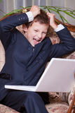 Angry business boy screaming at the computer Stock Photo