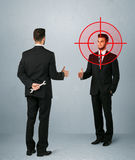 Angry business concept. Ruthless businessman handshake with a hiding weapon and a head target point Royalty Free Stock Photos