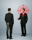 Angry business concept. Ruthless businessman handshake with a hiding weapon and a head target point Royalty Free Stock Photography