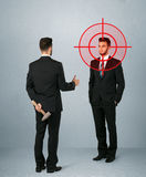 Angry business concept. Ruthless businessman handshake with a hiding weapon and a head target point Stock Photo