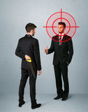 Angry business concept. Ruthless businessman handshake with a hiding weapon and a head target point Royalty Free Stock Images