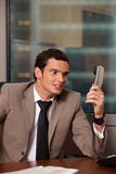 Angry business man holding telephone receiver Stock Images