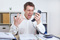 Angry business man screaming at. Phone in his office Royalty Free Stock Photo