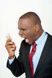 Angry business man screaming on cell phone Stock Photo