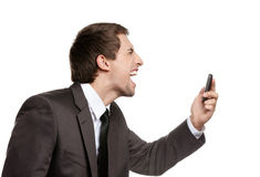 Angry business man screaming on cellphone. Angry business man screaming on cell mobile phone, concept of executive yelling, conversation problem and Stock Images