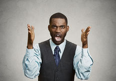 Angry business man screaming. Closeup portrait angry man with hands in air, wide open mouth yelling,  black background. Negative emotion, facial expression Royalty Free Stock Image