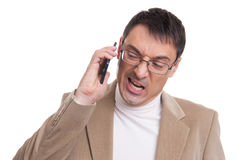 Angry business man screaming on mobile phone. Angry business man screaming on cell mobile phone, isolated over white background Royalty Free Stock Photo