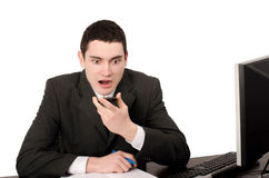 Business man sitting at desk yelling on the phone. Royalty Free Stock Image