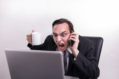 Angry business man talking on a cell phone and screaming on his laptop in the office Stock Images