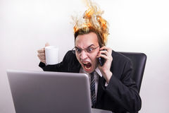 Angry business man talking on a cell phone and screaming on his laptop in the office, while his head is burning Royalty Free Stock Photo