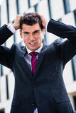 Angry business man tearing hair in despair Stock Images