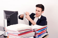 Angry business man tearing up paper work. Royalty Free Stock Image