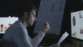 Angry business man throwing document paper on computer table in dark office. Nervous business analyst working overtime with financial reports in late office stock video