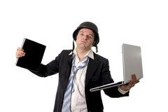Angry business man wearing helmet holding laptop and tablet Stock Images