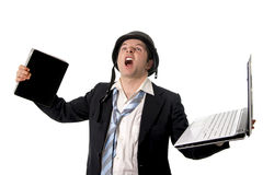 Angry business man wearing helmet holding laptop and tablet Royalty Free Stock Image