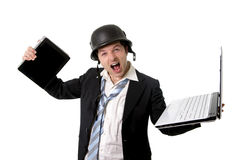 Angry business man wearing helmet holding laptop and tablet Royalty Free Stock Photo