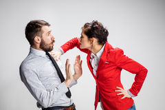 The angry business man and woman conflicting on a gray background Royalty Free Stock Photos