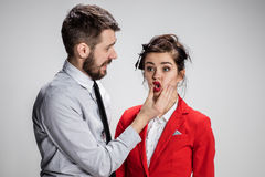 The angry business man and woman conflicting on a gray background stock image