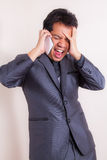 Angry business man yelling at mobile phone stock photo