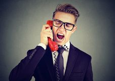 Angry young business man yelling on the phone. Angry business man yelling on the phone isolated on gray wall background Stock Photo