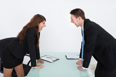 Angry Business People Shouting At Each Other. Side view of angry business people shouting at each other in office Stock Photo