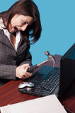 Angry business woman. Hitting the laptop with a hammer royalty free stock photo