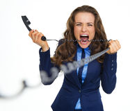 Angry business woman biting phone cord Royalty Free Stock Images