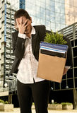 Angry Business Woman carrying Cardboard Box fired from Job outdoors in business district Royalty Free Stock Photos