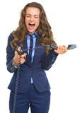 Angry business woman cutting phone handset with scissors Royalty Free Stock Photo