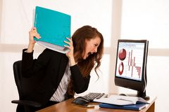 Angry business woman expressing rage at her desk in the office.  Stock Images