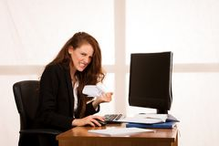 Angry business woman expressing rage at her desk in the office.  Royalty Free Stock Image
