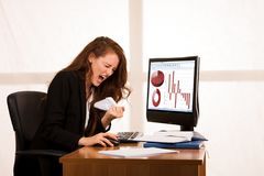 Angry business woman expressing rage at her desk in the office.  Stock Photo