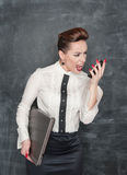 Angry business woman with laptop and mobile phone Stock Photo