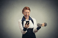 Angry business woman screaming on mobile phone lifting dumbbell Royalty Free Stock Images