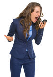 Angry business woman shouting in cell phone. Isolated on white Royalty Free Stock Image