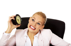 Angry business woman sitting behind the desk and shaking alarm clock royalty free stock images