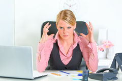 Angry business woman sitting at office desk royalty free stock images