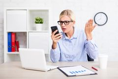 Angry business woman with smart phone in office Royalty Free Stock Photos