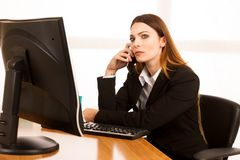Angry business woman talks on smert phone in office at her desk.  Royalty Free Stock Image