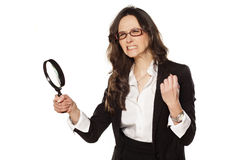 Angry business woman. Is very upset with and a magnifying glass in hand royalty free stock image