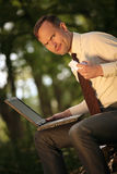Angry businessman. With laptop folding paper in park Royalty Free Stock Photos