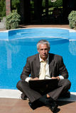 Angry businessman. Sitting next to swimming pool and using laptop computer Royalty Free Stock Photos