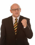 Angry businessman. Angry middle aged businessman with raised clenched fist, white background Royalty Free Stock Photo