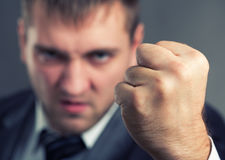 Angry businessman. Threaten with a fist Royalty Free Stock Images