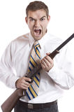 Angry Businessman. Angry man clutching a rifle and screaming Royalty Free Stock Images
