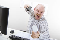 Angry Businessman Aiming Gun On Mobile Phone At Desk Royalty Free Stock Photo
